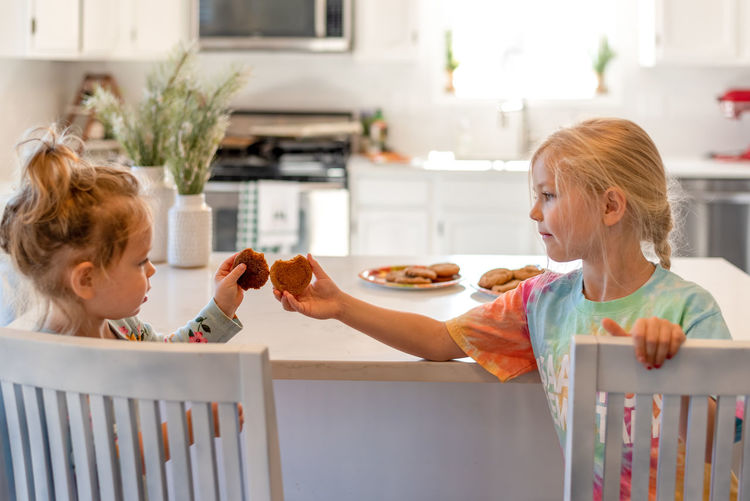 Women holding food in kitchen