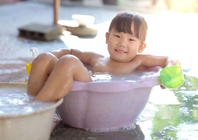 Little girl is smiling and playing water in the plastic basin happily in the garden. Childhood Child Smiling One Person Portrait Front View Males  Looking At Camera Happiness Real People Wet Water Domestic Room Shirtless Domestic Bathroom Lifestyles Innocence Outdoors
