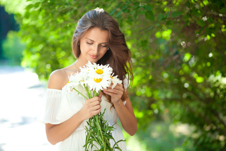 Attractive young woman in a white summer dress holding a bouquet of daisies Nature Flower Hair Beauty Day Outdoors Beautiful Woman Plant Bouquet Long Hair Fragility Hairstyle Freshness Beauty In Nature Holding Flower Arrangement Vulnerability  Young Adult One Person Flowering Plant Young Women Waist Up Focus On Foreground Real People Vulnerability  Lifestyles Leisure Activity Front View Women Flower Head