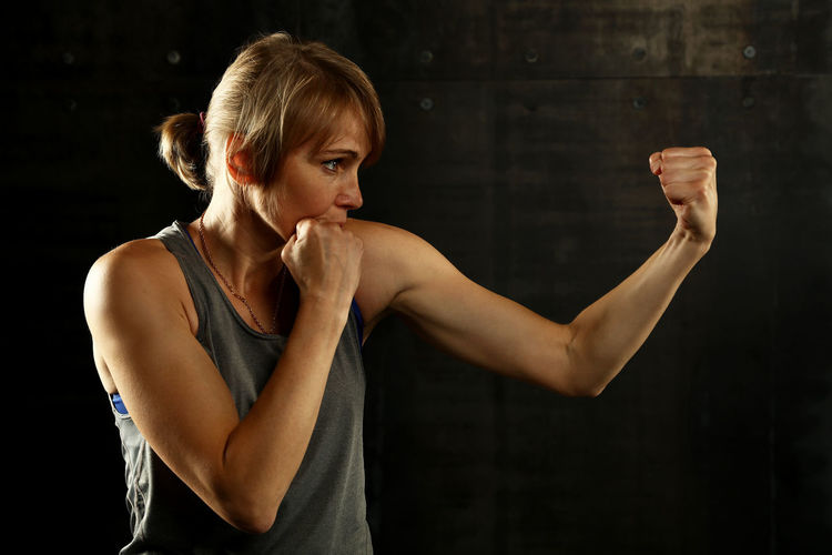 Athletic woman with arms raised in boxing stance over dark background Athletic Boxing Fight Power Adult Beautiful Woman Black Background Boxing - Sport Combat Exercising Femininity Fist Human Arm Indoors  Lifestyles Muscular Build One Person Portrait Side View Sport Stance Standing Strength Women Young Adult Be Brave A New Beginning Exploring Fun