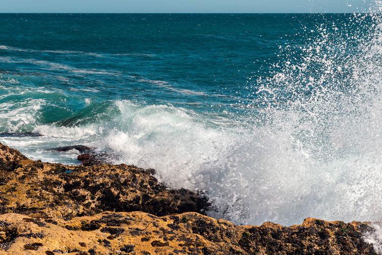 Waves splashing on rocks at sea shore