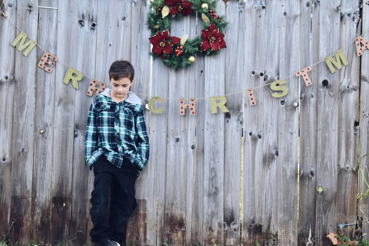 Full length of boy standing against wooden fence during christmas