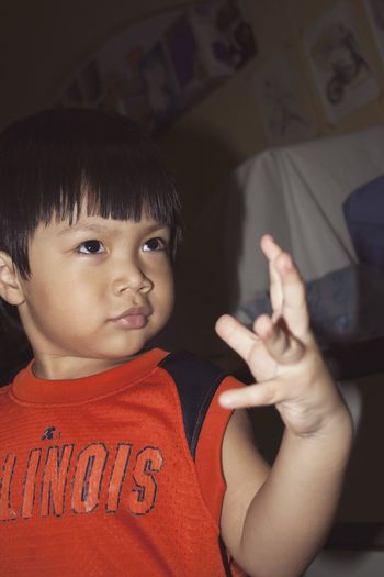 Close-up of cute boy gesturing at home