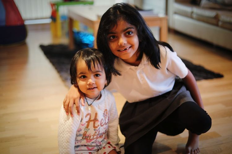 Cute sisters sitting on hardwood floor at home