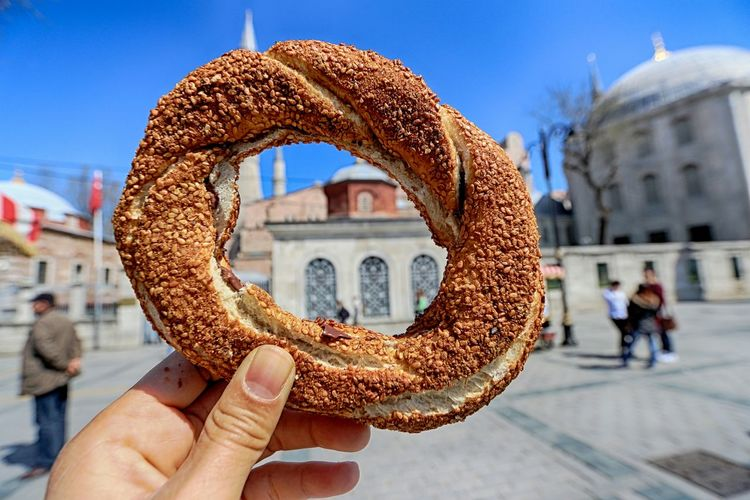 Cropped hand holding bread against hagia sophia