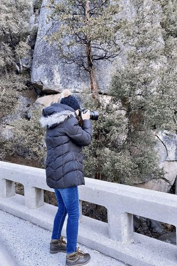 Rear view of woman standing by railing during winter