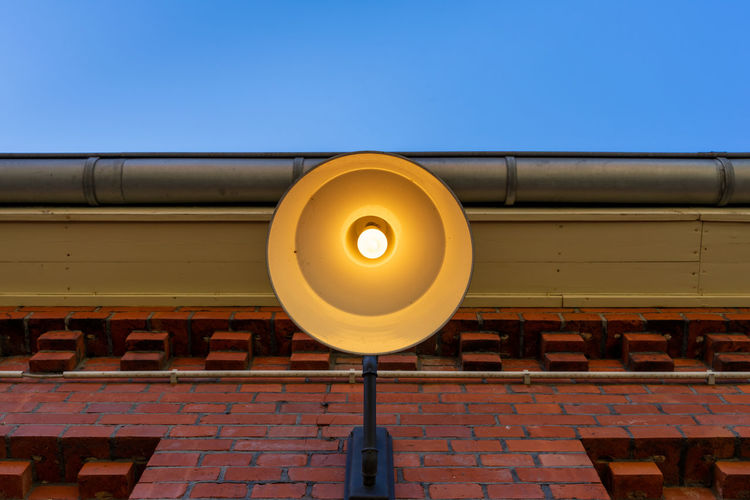 Low angle view of illuminated lamp against clear sky