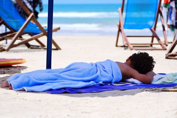 Boy Wrapped In Towel Lying At Beach