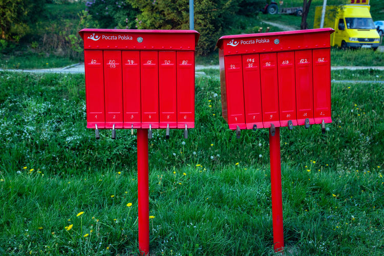 Communication Correspondence Day Field Grass Green Color Growth Guidance Land Letter Mail Mailbox Nature No People Outdoors Plant Post Boxes Public Mailbox Red Red Color Sign Text