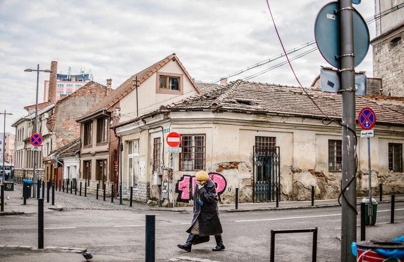 Woman walking on street against building in city