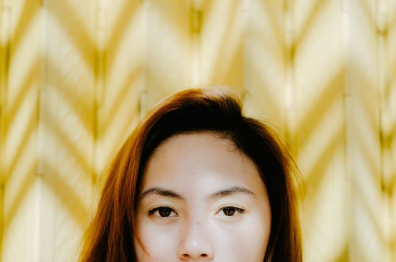 Close-up portrait of woman against yellow background