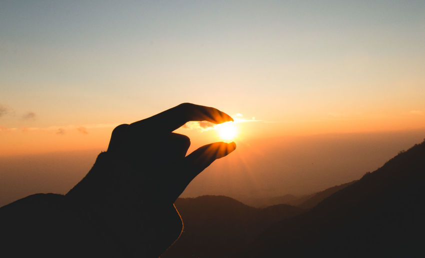 Optical Illusion Of Silhouette Person Holding Sun Over Mountains During Sunset