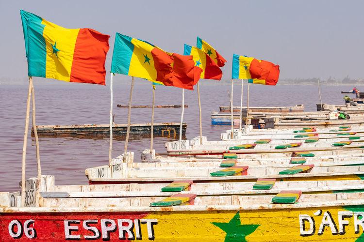 Multi colored flags on beach against sky