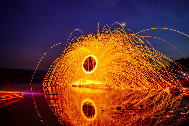 Reflection Of Wire Wool On Lake Against Sky