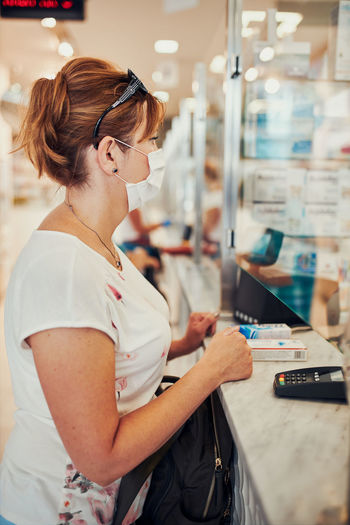Side view of woman wearing mask standing at chemist