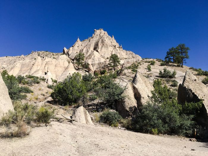 Clear Sky Tree Scenics Mountain Tranquil Scene Blue Rock Formation Beauty In Nature Tranquility Non-urban Scene Physical Geography Nature Geology Remote Tourist Travel Destinations Tourism Eroded Mountain Range Rocky Mountains Kasha-Katuwe Tent Rocks National Monument Beauty In Nature No People