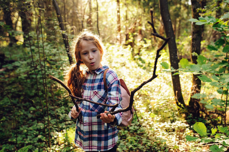 happy kid girl playing in summer forest with bow and arrows made from sticks Tree Forest Plant One Person Nature Casual Clothing Child Outdoors Exploring WoodLand Woods Travel Walk Summer Camping Wild Childhood Girl Playing Bow And Arrow Imagination Earth Day Little Explorer Adventure