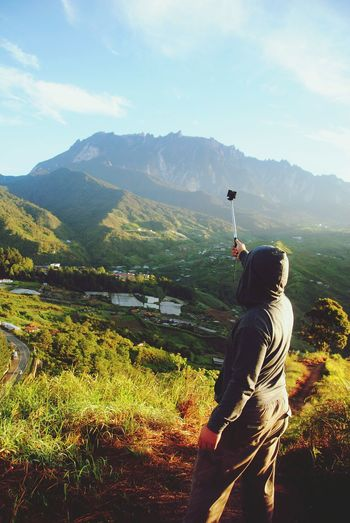 Rear View Of Man Taking Selfie Against Mountains