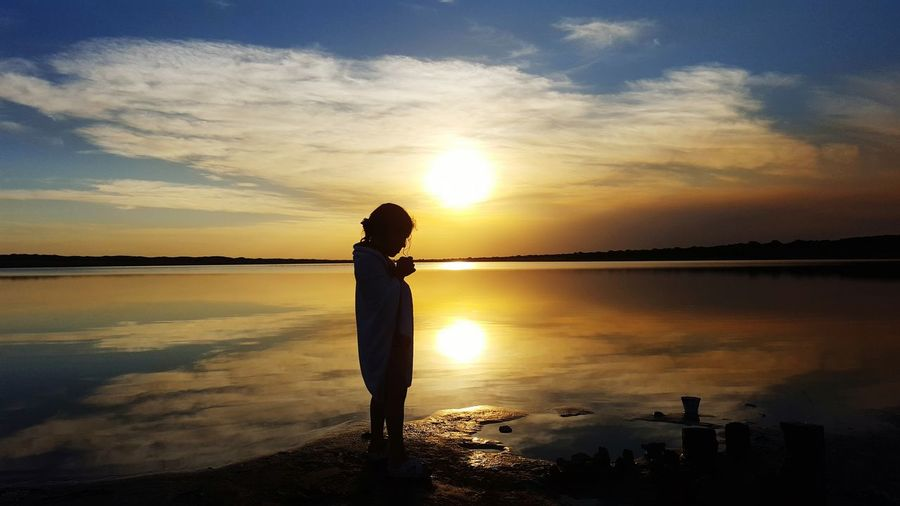 Silhouette Of A Girl Standing On Shore Against Sky During Sunset