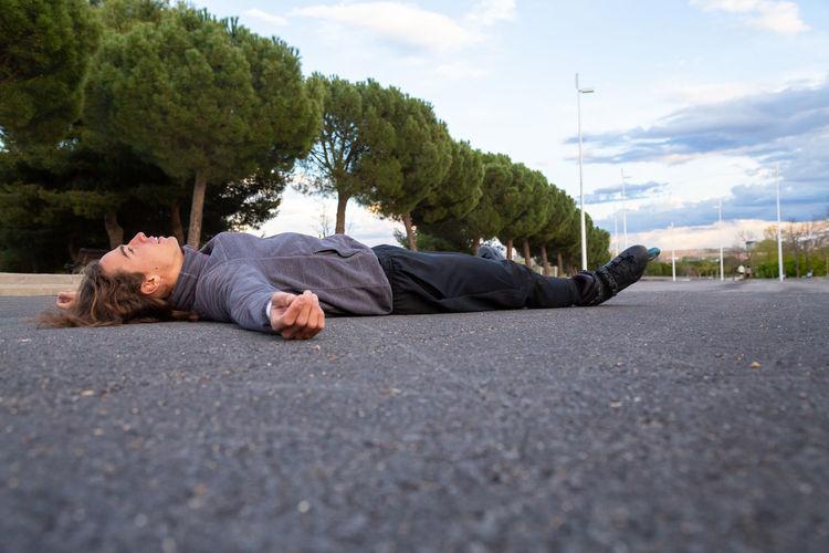 Man lying on road in city against sky