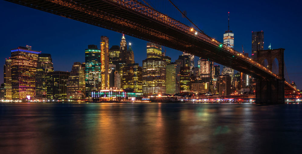 View on the Manhattan skyline and the Brooklyn bridge, NY Building Exterior Architecture Built Structure Illuminated City Night Skyscraper Building Water Waterfront Urban Skyline Travel Destinations Cityscape No People Modern Bridge - Man Made Structure Financial District  Tall - High Landscape Reflection New York Manhattan Brooklyn Bridge  Blue Hour Long Exposure