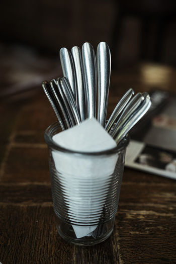 Close-up of spoons with tissue paper in glass on table