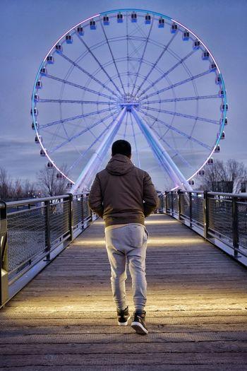 Rear View Of Man Walking On Footbridge Leading Towards Ferries Wheel