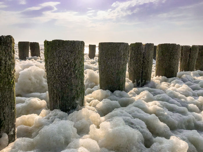 Wave splashing on wooden posts in sea