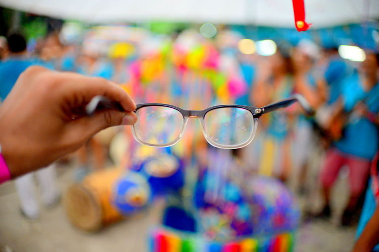 Cropped hand holding eyeglasses during carnival