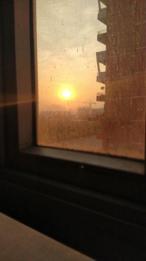 Buildings seen through wet glass window during sunset