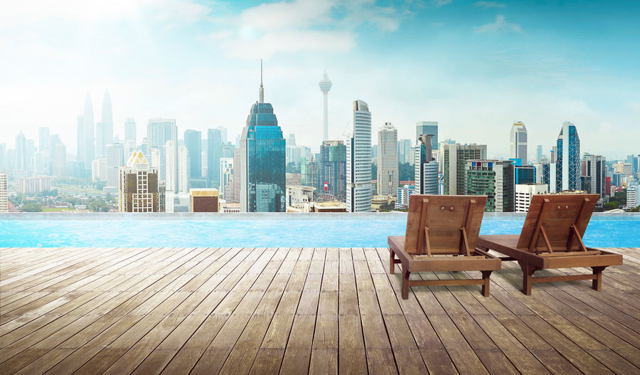 Chairs by swimming pool against cityscape