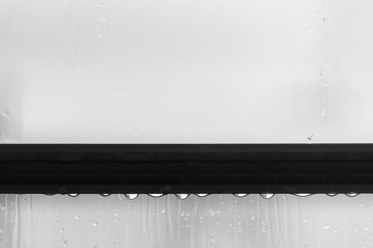 Close-up of raindrops on a window Copy Space Close-up No People Day White Background Minimalism Weather Rain RainDrop Wet Window Transparent Indoors  Glass - Material Backgrounds Architecture Wood - Material Rainy Season Atmospheric Mood Simplicity Black And White Drop Nature Motion Water