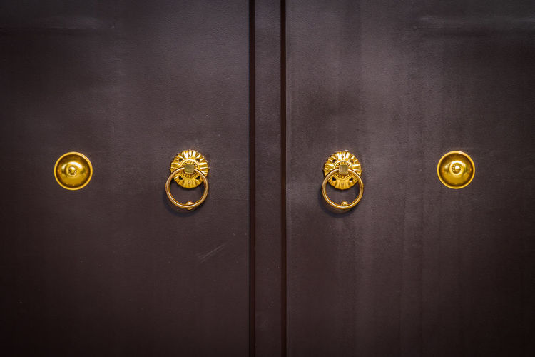 Close-up of closed wooden doors with golden handles