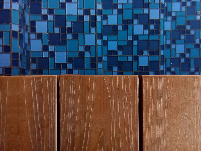 Close-Up Of Wooden Door Against Tiled Wall In Bathroom