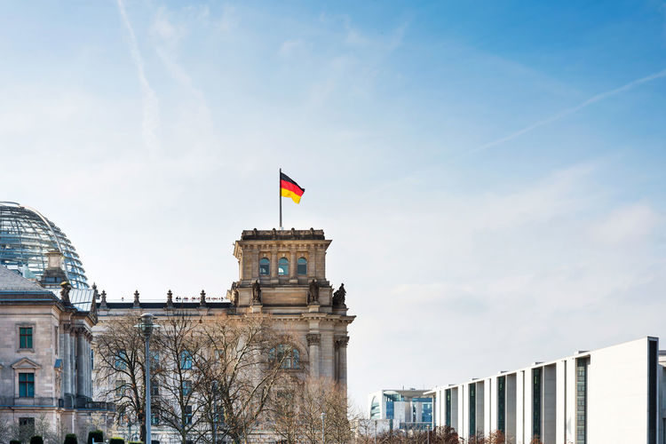 Low angle view of german flag on the reichstag against sky
