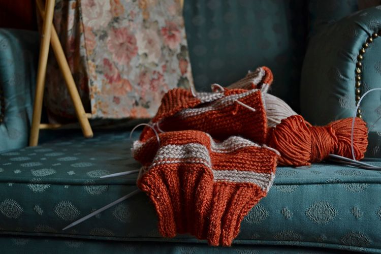 Close-Up Of Wool And Knitting Needle On Sofa