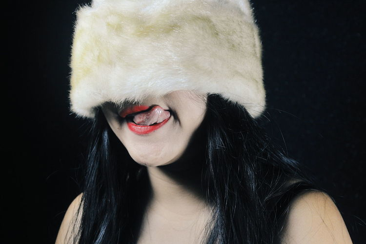 Close-Up Of Woman Sticking Out Tongue Against Black Background