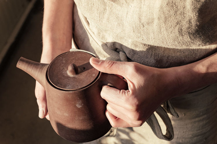 Midsection of woman holding tea kettle
