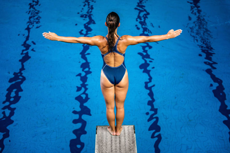 Female Diver Standing On The Jumping Board Diving Diver Swimming Pool Woman Water Sport Training Competition Young Exercising Diving Board Board Above Action Swimwear Blue Activity Muscular Build Extreme Sports Caucasian Ethnicity Athlete Jumping Standing Concentration Arms Outstretched