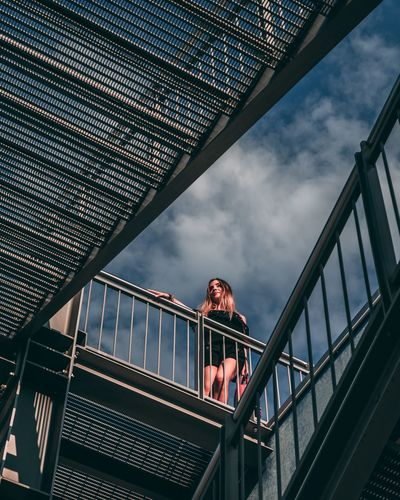 Low angle view of woman standing on bridge against sky