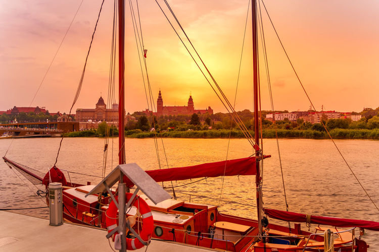 Sailboats moored on river against sky during sunset