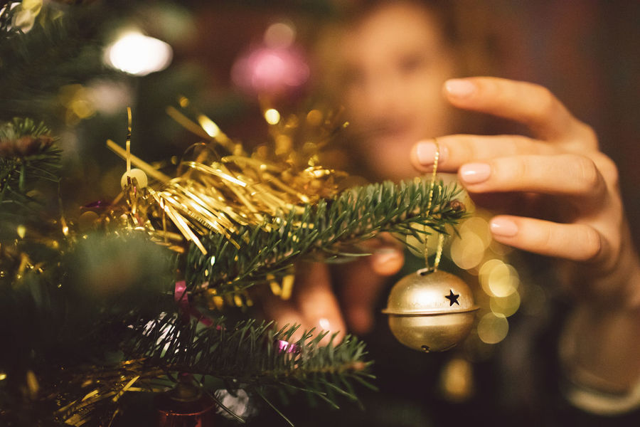 Curly Hair Girl Celebration Christmas Holiday Christmas Decoration christmas tree Human Hand Hand One Person Close-up Christmas Ornament Decoration Human Body Part Real People Focus On Foreground Selective Focus Holding Celebration Event Holiday - Event Gold Colored Finger