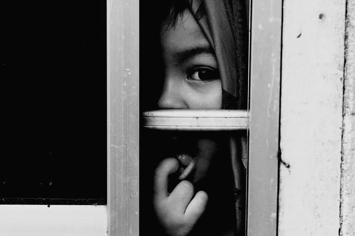 Portrait of boy with finger in mouth looking through window