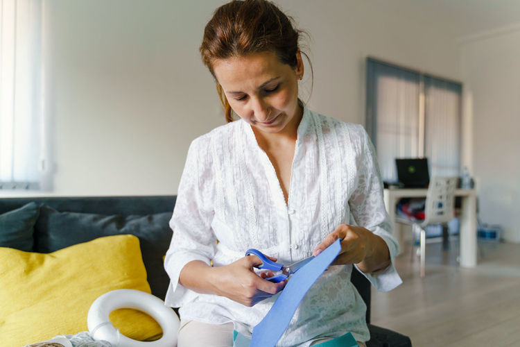 Mid adult woman holding while sitting at home