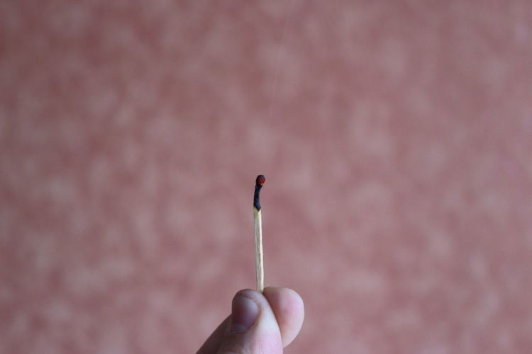 Close-up of fingers holding burning matchstick