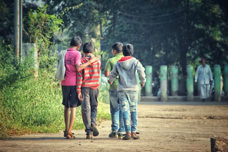 Rear view of boys walking on footpath