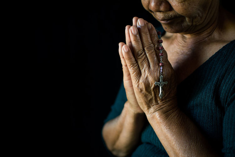 Midsection of senior woman holding rosary praying against black background