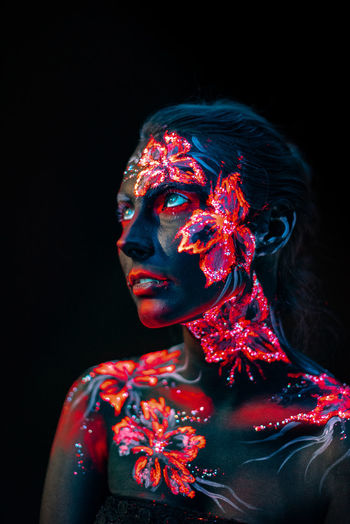 Young woman with paint on her body against black background