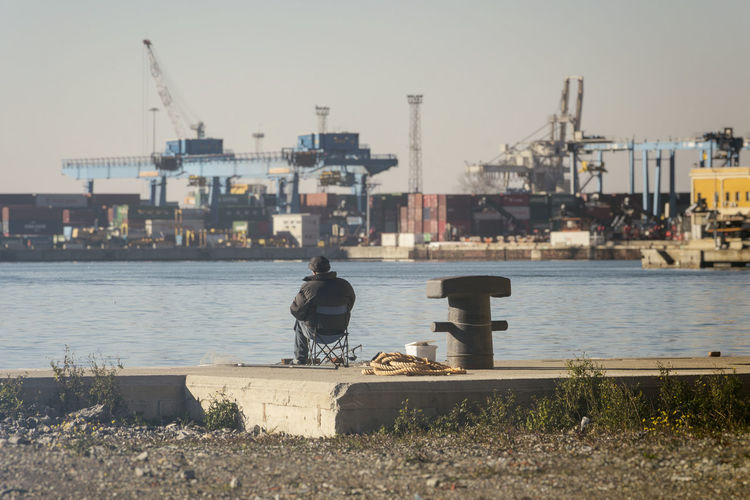 Rear view of man sitting on pier at harbor