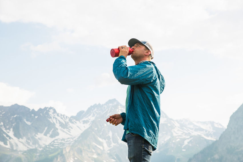 Man drinking water along the Tour du Mont Blanc Alps Italy Backpacking Drinking Water Hiking Hydration Tour Du Mont Blanc Adult Hikingadventures Italy Leisure Activity Lifestyles Men Mountain Mountain Range One Person Outdoors Scenics - Nature Water Water Bottle